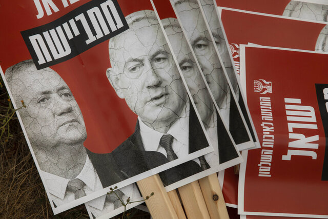 FILE - In this May 14, 2020 file photo, signs depict Israeli Prime Minister Benjamin Netanyahu and Blue and White party leader Benny Gantz, during a demonstration outside the Knesset, Israel's parliament in Jerusalem. Netanyahu faces a midnight deadline Monday, Aug. 24, 2020, to work out a budget deal with Gantz, his main rival or plunge the country into a fourth election in under two years. While the budget battle is the immediate cause of the crisis, Monday's showdown is rooted in the power-sharing arrangement between Netanyahu and Gantz. Hebrew reads: