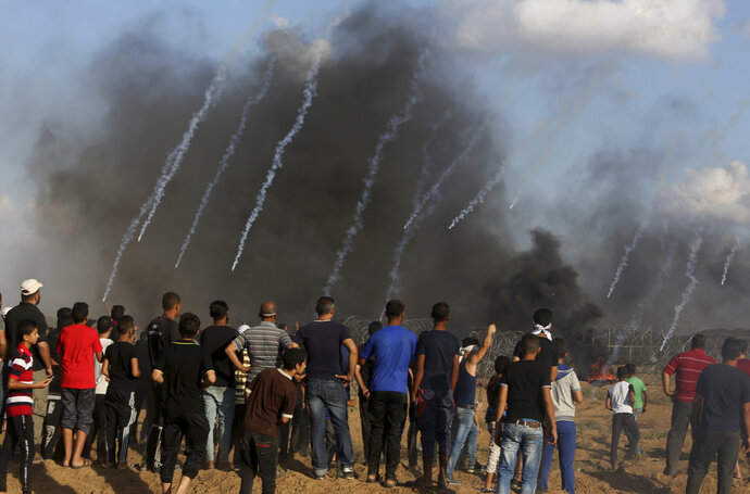 Protester burn tires while Israeli troops fire teargas near the fence of Gaza Strip border with Israel, during a protest east of Gaza City, east of Gaza City, Friday, Sept. 7, 2018. A teenager was killed and dozens of other Palestinians injured by Israeli fire at a border protest, Gaza officials said. (AP Photo/Adel Hana)