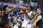 Washington forward Isaiah Stewart (33) loses the ball as he tries to shoot between Oregon State guard Ethan Thompson (5) and forward Tres Tinkle during the first half of an NCAA college basketball game Thursday, Jan. 16, 2020, in Seattle. (AP Photo/Ted S. Warren)
