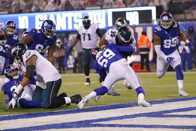 Philadelphia Eagles running back Boston Scott (35) scores a touchdown in front of New York Giants linebacker Lorenzo Carter (59) in the second half of an NFL football game, Sunday, Dec. 29, 2019, in East Rutherford, N.J. (AP Photo/Seth Wenig)