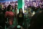 In this Tuesday, Dec. 3, 2019, photo, model Winnie Harlow, from left, singer Maluma, Kourtney Kardashian and Kim Kardashian wait for the Christian Dior pre-fall 2020 men's fashion show to start during Miami Art week, in Miami. (AP Photo/Brynn Anderson)
