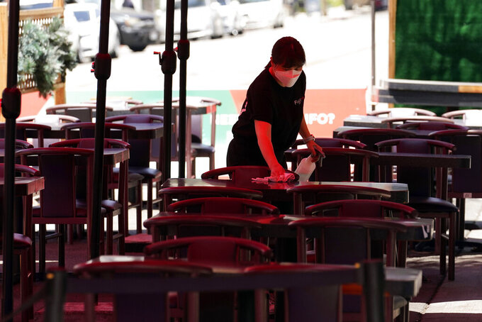 Tables are cleaned in an outdoor eating area amid the COVID-19 pandemic Tuesday, May 18, 2021, in Burbank, Calif. (AP Photo/Marcio Jose Sanchez)