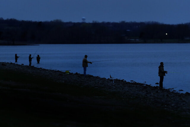 People maintain their distance as they fish on the first day of a stay-at-home order Monday, March 30, 2020 at Hillsdale Lake near Hillsdale, Kan. The statewide order was the latest measure enacted by Kansas Gov. Laura Kelly in an attempt to curb the spread of the new coronavirus. (AP Photo/Charlie Riedel)