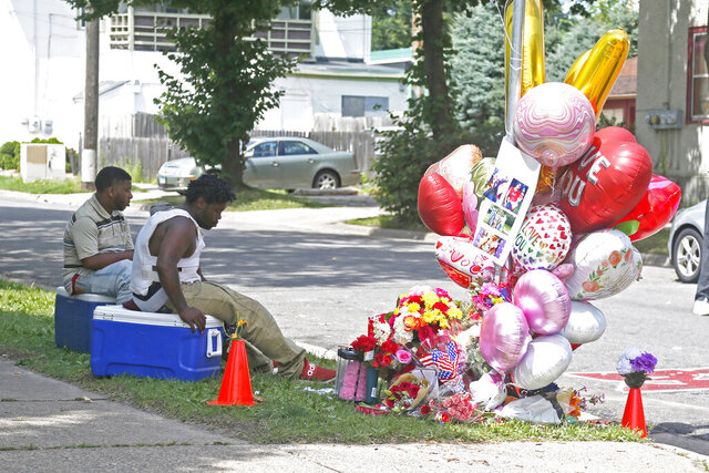 Two men sit Tuesday, July 7, 2020 at a memorial for a pregnant woman who was shot in south Minneapolis Sunday and died after being rushed to a hospital. Doctors at the Hennepin County Medical Center delivered the baby of the shooting victim who was in a vehicle when she was shot and later pronounced dead, according to authorities.The baby girl was placed in intensive care. (AP Photo/Jim Mone)