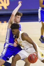 Notre Dame's Trey Wertz (2) moves by Duke's Matthew Hurt during the first half of an NCAA college basketball game Wednesday, Dec. 16, 2020, in South Bend, Ind. (AP Photo/Robert Franklin)