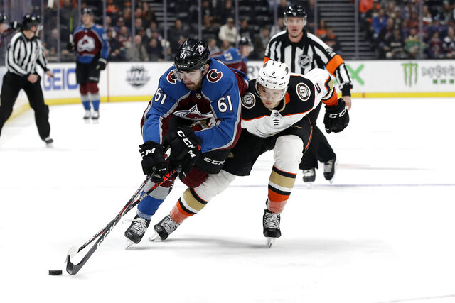 Colorado Avalanche's Martin Kaut, left, is defended by Anaheim Ducks' Brendan Guhle during the first period of an NHL hockey game Friday, Feb. 21, 2020, in Anaheim, Calif. (AP Photo/Marcio Jose Sanchez)