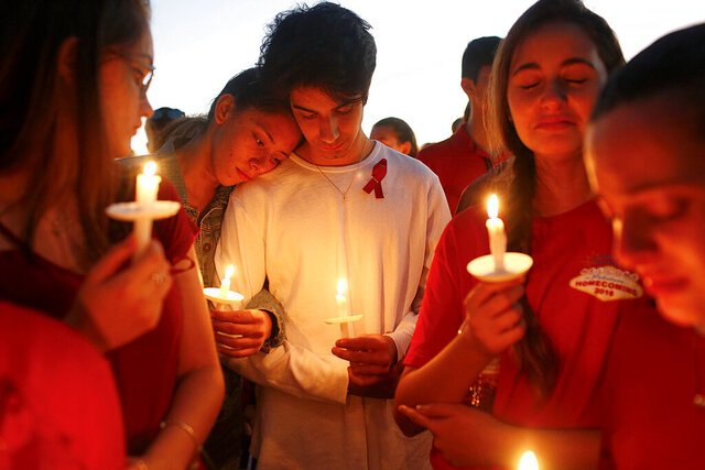 FILE- In this Feb. 15, 2018, file photo, students gather during a vigil at Pine Trails Park for the victims of a shooting at Marjory Stoneman Douglas High School, in Parkland, Fla. Nikolas Cruz, a former student, was charged with 17 counts of premeditated murder. For Florida, the 2010s were a decade of high-profile mass shootings at a nightclub, high school, airport and naval base, leaving 74 victims dead. (AP Photo/Brynn Anderson, File)
