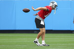 Carolina Panthers quarterback Sam Darnold tries to catch a football behind his back during a Fan Fest practice at the NFL team's training camp in Charlotte, N.C., Friday, Aug. 6, 2021. (AP Photo/Nell Redmond)