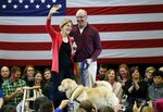 Sen. Elizabeth Warren, D-Mass., left, stands on stage with her husband, Bruce Mann, and their dog, Bailey, during an organizing event at Manchester Community College in Manchester, N.H., Saturday, Jan.12, 2019. (AP Photo/Michael Dwyer)