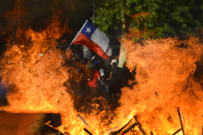 Seen through a burning street barricade, an anti-government demonstrator waves a Chilean flag in Santiago, Chile, Monday, Oct. 28, 2019. Fresh protests and attacks on businesses erupted in Chile Monday despite President Sebastián Piñera's replacement of eight important Cabinet ministers with more centrist figures, and his attempts to assure the country that he had heard calls for greater equality and improved social services. (AP Photo/Matias Delacroix)