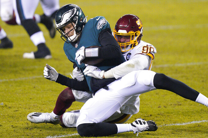 Philadelphia Eagles' Nate Sudfeld, left, is sacked by Washington Football Team's Montez Sweat during the second half of an NFL football game, Sunday, Jan. 3, 2021, in Philadelphia. (AP Photo/Chris Szagola)