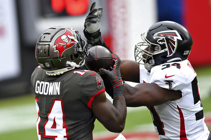 Tampa Bay Buccaneers wide receiver Chris Godwin (14) beats Atlanta Falcons linebacker Foye Oluokun (54) on a 7-yard touchdown reception during the first half of an NFL football game Sunday, Jan. 3, 2021, in Tampa, Fla. (AP Photo/Jason Behnken)