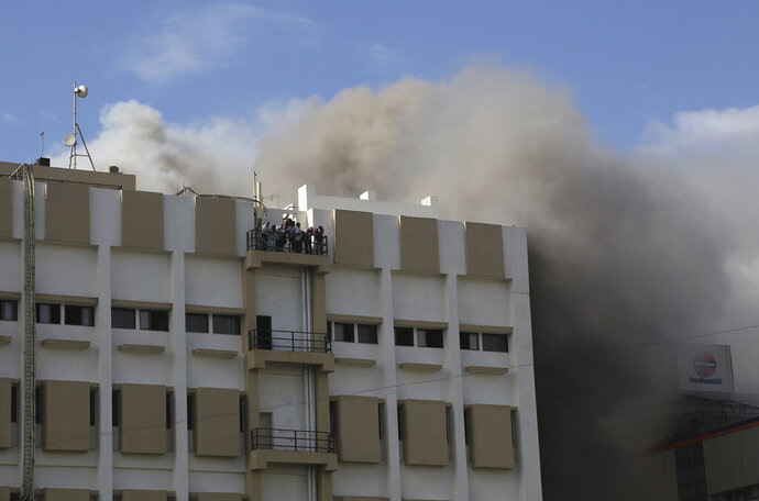 People awaiting rescue stand on the balcony of a nine-story building with offices of a state-run telephone company during a fire in Mumbai, India, Monday, July 22, 2019. (AP Photo/Rafiq Maqbool)