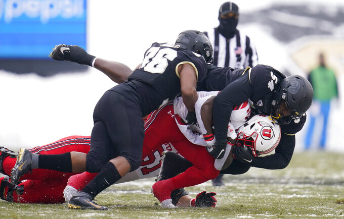 Utah wide receiver Kyrese Rowan, bottom right, is stopped by Colorado defensive end Terrance Lang, top right, and linebacker Akil Jones during the first half of an NCAA college football game Saturday, Dec. 12, 2020, in Boulder, Colo. (AP Photo/David Zalubowski)