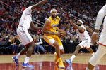 Los Angeles Lakers center JaVale McGee (7) drives between Houston Rockets center Clint Capela, left, and guard James Harden during the first half of an NBA basketball game Saturday, Jan. 18, 2020, in Houston. (AP Photo/Michael Wyke)