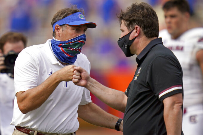 Florida head coach Dan Mullen, left, and South Carolina head coach Will Muschamp bump fists at the end of an NCAA college football game, Saturday, Oct. 3, 2020, in Gainesville, Fla. (AP Photo/John Raoux, Pool)