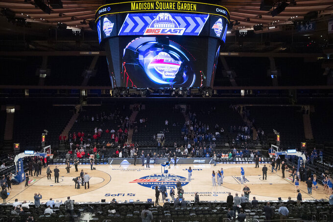Madison Square Garden workers are shown at the NCAA college basketball men's Big East Conference tournament Thursday, March 12, 2020, in New York. The major conferences in college sports have all canceled their basketball tournaments because of the new coronavirus, putting the celebrated NCAA Tournament in doubt. (AP Photo/Mary Altaffer)