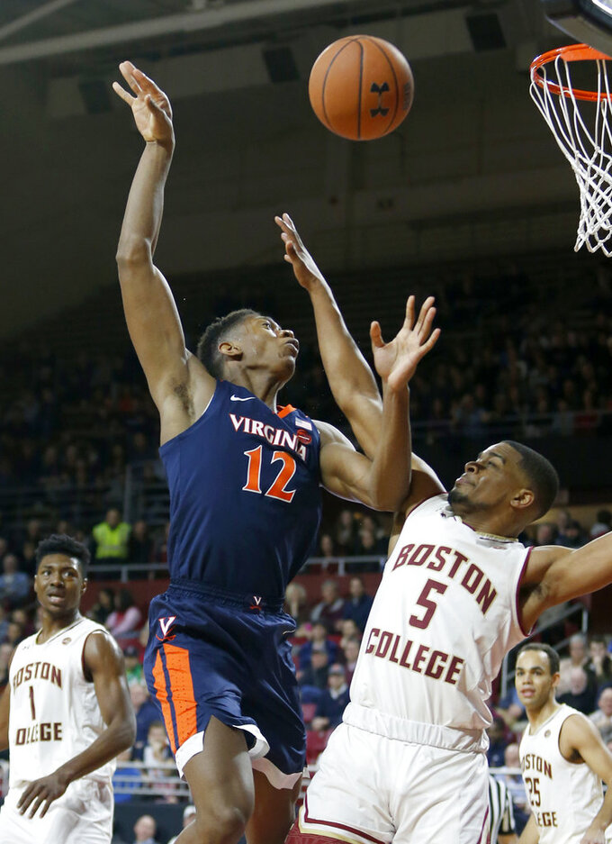 Virginia guard De'Andre Hunter (12) is fouled as he drives to the basket against Boston College guard Wynston Tabbs (5) during the first half of an NCAA college basketball game Wednesday, Jan. 9, 2019, in Boston. (AP Photo/Mary Schwalm)