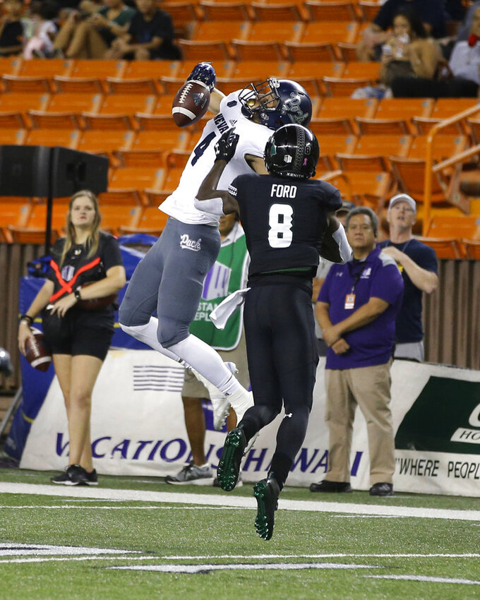 Nevada wide receiver Elijah Cooks (4) fails to catch as Hawaii defensive back Eugene Ford (8) tries to pressure during the first half of an NCAA college football game Saturday, Oct. 20, 2018, in Honolulu. (AP Photo/Marco Garcia)
