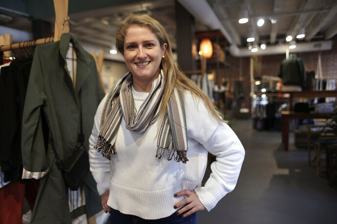 In this Thursday, Nov. 14, 2019, photo, Annie Venditti, vice president of operations at clothing retailer American Rhino, stands for a photograph in the store, in Faneuil Hall Marketplace, in Boston. At the age of 23, Venditti was learning about the complexities of building and liquor laws. The company did the smart thing, and got a consultant to guide them. (AP Photo/Steven Senne)