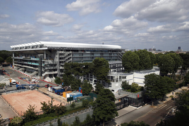 The Philippe-Chatrier tennis court with its retractable roof is pictured from a top building in Paris, Sunday, May 24, 2020 as the Roland Garros tournament is posponed. It should have been the first day of the French Open tennis tournament, with thousands of fans flocking to Roland Garros in western Paris hoping to catch a glimpse of 12-time champion Rafael Nadal or No. 1 Novak Djokovic. Instead, the grounds are deserted amid the coronavirus pandemic, with the famed tennis tournament on hold until late September. (AP Photo/Francois Mori)