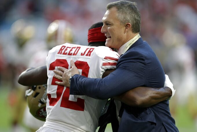 San Francisco 49ers general manager John Lynch, right, embraces D.J. Reed Jr., on the field before the NFL Super Bowl 54 football game against the Kansas City Chiefs Sunday, Feb. 2, 2020, in Miami Gardens, Fla. (AP Photo/Chris O'Meara)