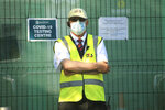 A security guard outside a Covid-19 testing centre, in Bradford, West Yorkshire, England, Friday July 31, 2020. Britain's health secretary has defended a decision to reimpose restrictions on social life in a swath of northern England, saying it was important to keep ahead of the spread of COVID-19. Under the new restrictions, people from different households in Greater Manchester, England's second largest metropolitan area, have been asked to not meet indoors. The same orders applies to the surrounding areas of Lancashire and West Yorkshire counties. (Danny Lawson/PA via AP)