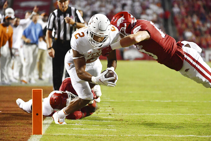 Texas running back Roschon Johnson (2) is knocked out of bounds just short of the end zone by Arkansas defenders Joe Foucha (7) and Bumper Pool (10) during the second half of an NCAA college football game Saturday, Sept. 11, 2021, in Fayetteville, Ark. (AP Photo/Michael Woods)