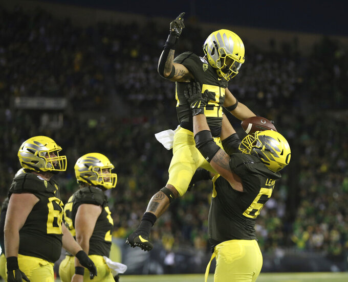 Oregon's Cyrus Habibi-Likio is hoisted in celebration by Shane Lemieux after scoring a touchdown against California during the third quarter of an NCAA college football game Saturday, Oct. 5, 2019, in Eugene, Ore. (AP Photo/Chris Pietsch)