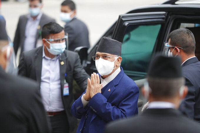 Nepal Prime Minister Khadga Prasad Oli, center, arrives at the parliament in Kathmandu, Nepal, Monday, May 10, 2021. Oli asked parliament for a vote of confidence on Monday in an attempt to show he still has enough support to stay in power despite an expected second split within his governing party. (AP Photo/Niranjan Shrestha)