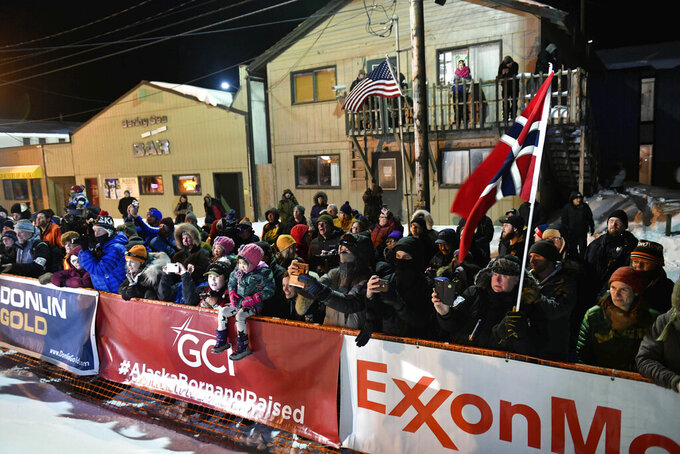 FILE - In this March 18, 2020, file photo, a crowd standing behind ExxonMobile signage watches as Thomas Waerner, of Norway, arrives in Nome, Alaska to win the Iditarod Trail Sled Dog Race. The world's most famous sled dog race has lost another major sponsor as the Iditarod prepares for a scaled-back version of this year's race because of the pandemic, officials said Thursday, Jan. 21, 2021. ExxonMobil confirmed to The Associated Press that the oil giant will drop its sponsorship of the race. (Marc Lester/Anchorage Daily News via AP, File)