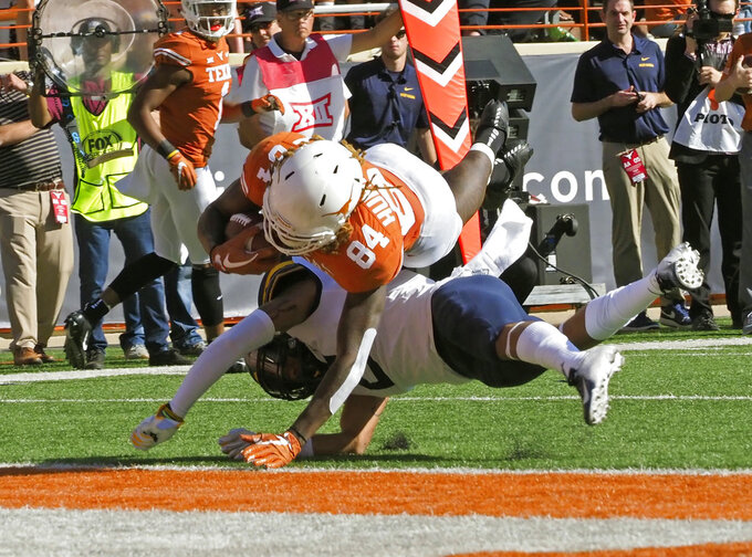 Texas receiver Lil'Jordan Humphrey (84) scores a touchdown against West Virginia defensive back Kenny Robinson, Jr. during the first half of an NCAA college football game, Saturday, Nov. 3, 2018, in Austin, Texas. (AP Photo/Michael Thomas)