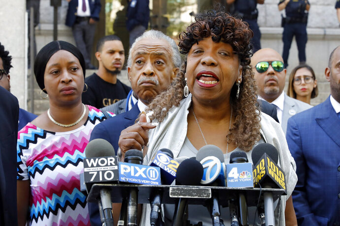 Gwen Carr, mother of chokehold victim Eric Garner, speaks outside the U.S. Attorney's office, in the Brooklyn borough of New York, Tuesday, July 16, 2019, as Rev. Al Sharpton listens, center.   Federal prosecutors won't bring civil rights charges against New York City police officer Daniel Pantaleo, in the 2014 chokehold death of Garner, a decision made by Attorney General William Barr and announced one day before the five-year anniversary of his death, officials said.  (AP Photo/Richard Drew)
