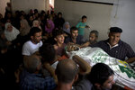 Palestinian mourners carry the body of a Hamas security forces member, Mahmoud al-Adham, 28, into the family home during his funeral in Town of Jabaliya, northern Gaza Strip, Thursday, July 11, 2019. Hamas' armed wing said Thursday that the Israeli army