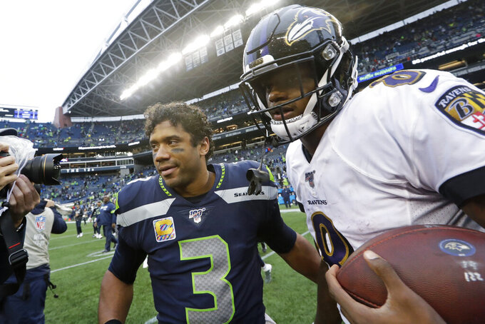 Baltimore Ravens quarterback Lamar Jackson, right, talks with Seattle Seahawks quarterback Russell Wilson (3) after an NFL football game, Sunday, Oct. 20, 2019, in Seattle. (AP Photo/Elaine Thompson)