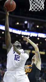 TCU's Kouat Noi (12) shoots under pressure from Oklahoma State's Thomas Dziagwa during the second half of an NCAA college basketball game in the Big 12 men's tournament Wednesday, March 13, 2019, in Kansas City, Mo. TCU won 73-70. (AP Photo/Charlie Riedel)