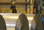 FILE- In this Feb. 15, 2013, file photo, an employee looks on from behind coils of steel as acting Secretary of Labor Seth Harris speaks to workers after a tour of ArcelorMittal Steel's hot dip galvanizing line in Cuyahoga Heights, Ohio. President Donald Trump's tariffs are expected to raise prices for steel and aluminum in this country. That will help domestic producers and could create several hundred new steelworker jobs. (AP Photo/Mark Duncan, File)