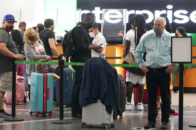 People wait in long lines to rent a vehicle at Miami International Airport, Friday, May 28, 2021, in Miami. The Greater Miami Convention and Visitors Bureau is anticipating hotel occupancy levels to surge above pre-pandemic levels. (AP Photo/Marta Lavandier)