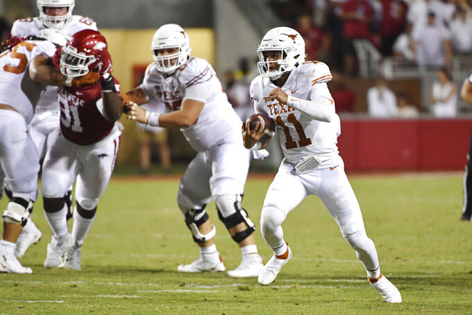 Texas quarterback Casey Thompson (11) scrambles out of the pocket during the second half of the team's NCAA college football game against Arkansas on Saturday, Sept. 11, 2021, in Fayetteville, Ark. (AP Photo/Michael Woods)
