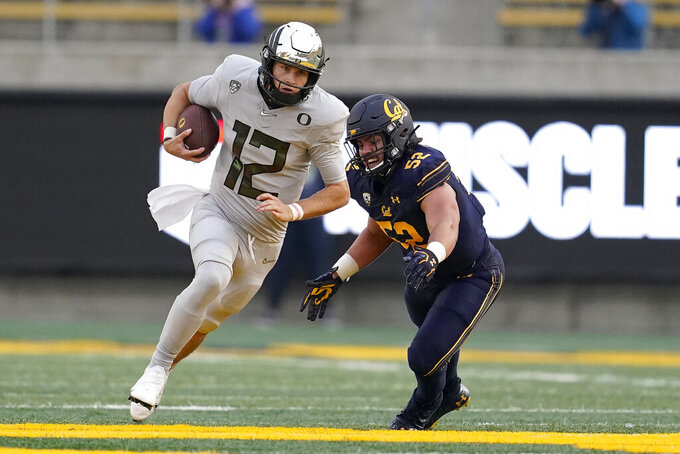 Oregon quarterback Tyler Shough (12) runs past California linebacker Braxten Croteau (52) during the first half of an NCAA college football game in Berkeley, Calif., Saturday, Dec. 5, 2020. (AP Photo/Jeff Chiu)