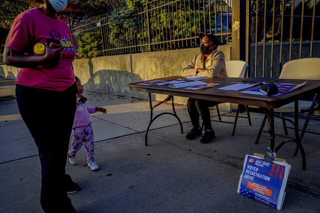 A woman and child walk past Laurae Caruth, right, volunteer with Christian Cultural Center Social Justice Initiative's voter registration drive, as she sits at a table where she registers voters, Friday, Sept. 18, 2020, in the Brooklyn borough of New York.