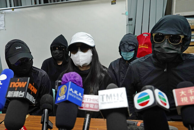 Relatives of 12 Hong Kong activists detained at sea by Chinese authorities, attend a press conference in Hong Kong, Monday, Dec. 28, 2020. Trials for 10 people accused of attempting to flee Hong Kong by speedboat amid a government crackdown on dissent got underway in China on Monday, a court official said. The defendants face charges of illegally crossing the border, while two face additional charges of organizing the attempt, according to an indictment issued in the southern city of Shenzhen. (AP Photo/Kin Cheung)