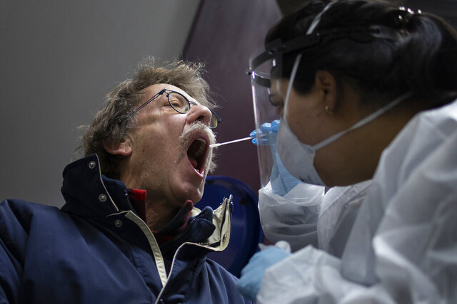 A man gets a nose and throat swab as residents of Bergschenhoek, Netherlands, take part in a mass coronavirus test of all of the municipality's 62,000 inhabitants starting Wednesday, Jan. 13, 2021, following a cluster of COVID-19 cases at an elementary school. (AP Photo/Peter Dejong)