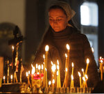 A woman lights a candle in memory of victims of shooting in the vocational college in Kerch, Crimea, in a church in St.Petersburg, Russia, Thursday, Oct. 18, 2018. An 18-year-old student strode into his vocational school in Crimea, Wednesday, then pulled out a shotgun and opened fire, killing 19 students and wounding more than 50 others before killing himself. (AP Photo/Dmitri Lovetsky)
