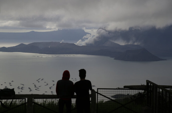 Men watch from Tagaytay, Cavite province, south of Manila, as Taal Volcano continues to spew ash on Tuesday, Jan. 14, 2020. Thousands of people fled the area through heavy ash as experts warned that the eruption could get worse and plans were being made to evacuate more.(AP Photo/Aaron Favila)