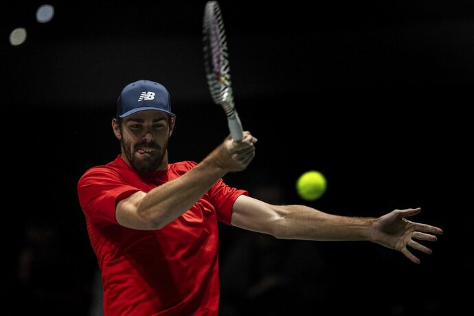 USA player Reilly Opelka returns the ball to Canada's Vasek Pospisil during their Davis Cup tennis match in Madrid, Spain, Tuesday, Nov. 19, 2019. (AP Photo/Bernat Armangue)