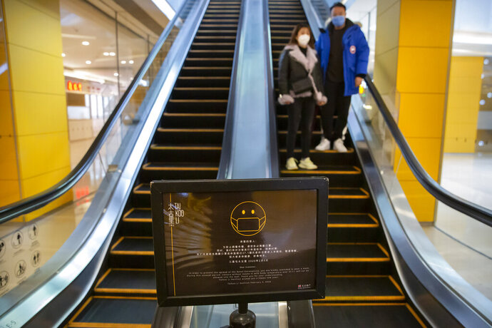 A sign reminds customers to wear face masks as a couple rides an escalator at a shopping center in Beijing, Friday, Feb. 14, 2020. China on Friday reported another sharp rise in the number of people infected with a new virus, as the death toll neared 1,400. (AP Photo/Mark Schiefelbein)