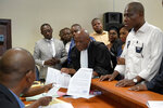 Accompanied by his wife and his lawyers, spurned Congo opposition candidate Martin Fayulu, right, petitions the constitutional court following his loss in the presidential elections in Kinshasa, Congo, Saturday Jan. 12, 2019. The ruling coalition of Congo's outgoing President Joseph Kabila has won a large majority of national assembly seats, the electoral commission announced Saturday, while the presidential election runner-up was poised to file a court challenge alleging fraud. (AP Photo/Jerome Delay)