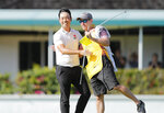Kevin Na, left, embraces caddie Kenneth Harms after winning the final round of the Sony Open golf tournament Sunday, Jan. 17, 2021, at Waialae Country Club in Honolulu. (Jamm Aquino/Honolulu Star-Advertiser via AP)