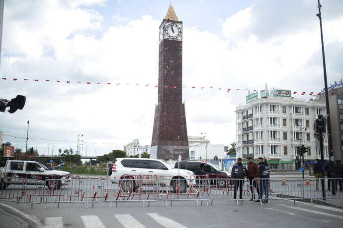 Security forces stand guard in Tunis' landmark Avenue Habib Bourgiba, where massive protests took place in 2011, on the tenth anniversary of the uprising, during a national lockdown after a surge in COVID-19 cases, in Tunis, Thursday, Jan. 14, 2021. Tunisia is commemorating the 10th anniversary since the flight into exile of its iron-fisted leader, Zine El Abidine Ben Ali, pushed from power in a popular revolt that foreshadowed the so-called Arab Spring. But there will be no festive celebrations Thursday marking the revolution in this North African nation, ordered into lockdown to contain the coronavirus.  (AP Photo/Mosa'ab Elshamy)